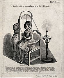 A_man_drawing_the_silhouette_of_a_seated_woman_on_translucen_Wellcome_V0049670